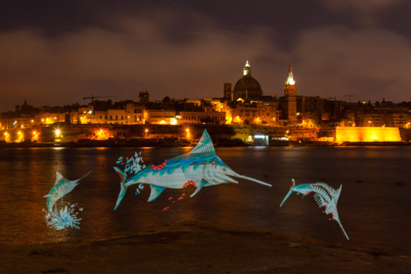 Maltese street artist Twitch create a spectacular light painting, depicting a swordfish leaping from of the waters surrounding Valletta while being consumed by humans. Twitch, in collaboration with Our Fish and Dancing Fox and has created the artwork to send a message to 20017 Our Ocean conference delegates that they must help protect Mediterranean sea life. Photo: Dave Walsh Photography